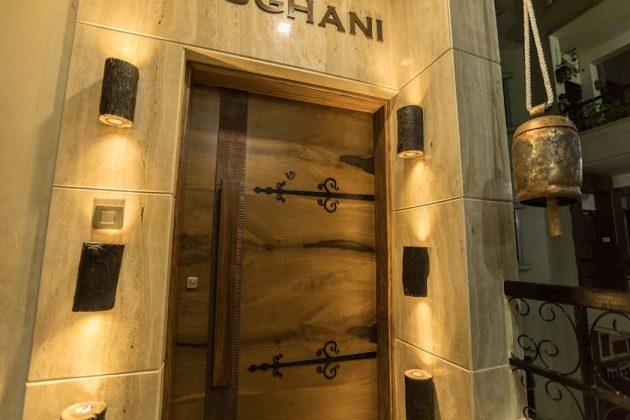 Деревянная дверь в обрамлении итальянского мрамора